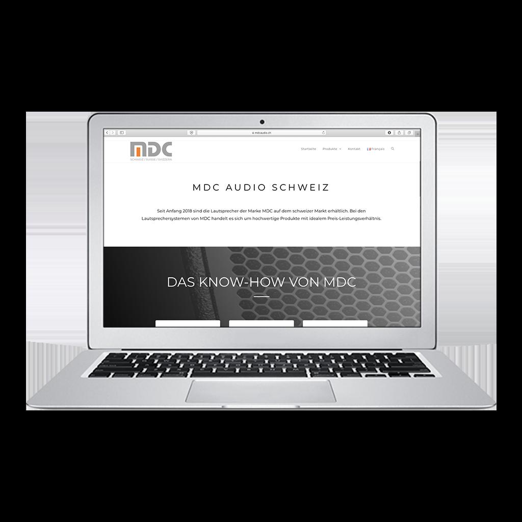 Webseite mdcaudio.ch von Kupfertext auf Macbook dargestellt.